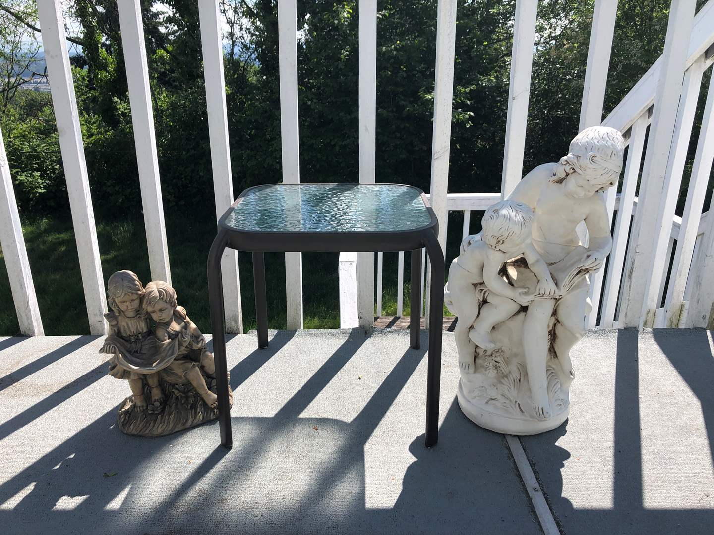 Lot # 217 - Outdoor Table w/ Glass Top & 2 Large Plastic Statues  (main image)