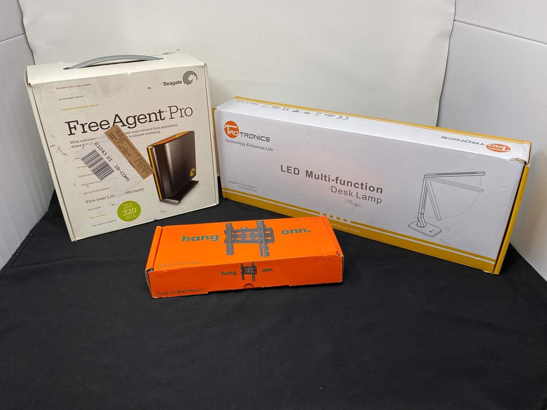 "Lot # 13 - New in Box Items: Free Agent Pro 320 gb Hard Drive, TaoTronics LED Desk Lamp, ""ONN"" TV Wall Mount (main image)"
