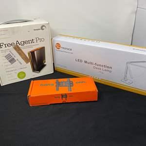 "Lot # 13 - New in Box Items: Free Agent Pro 320 gb Hard Drive, TaoTronics LED Desk Lamp, ""ONN"" TV Wall Mount"