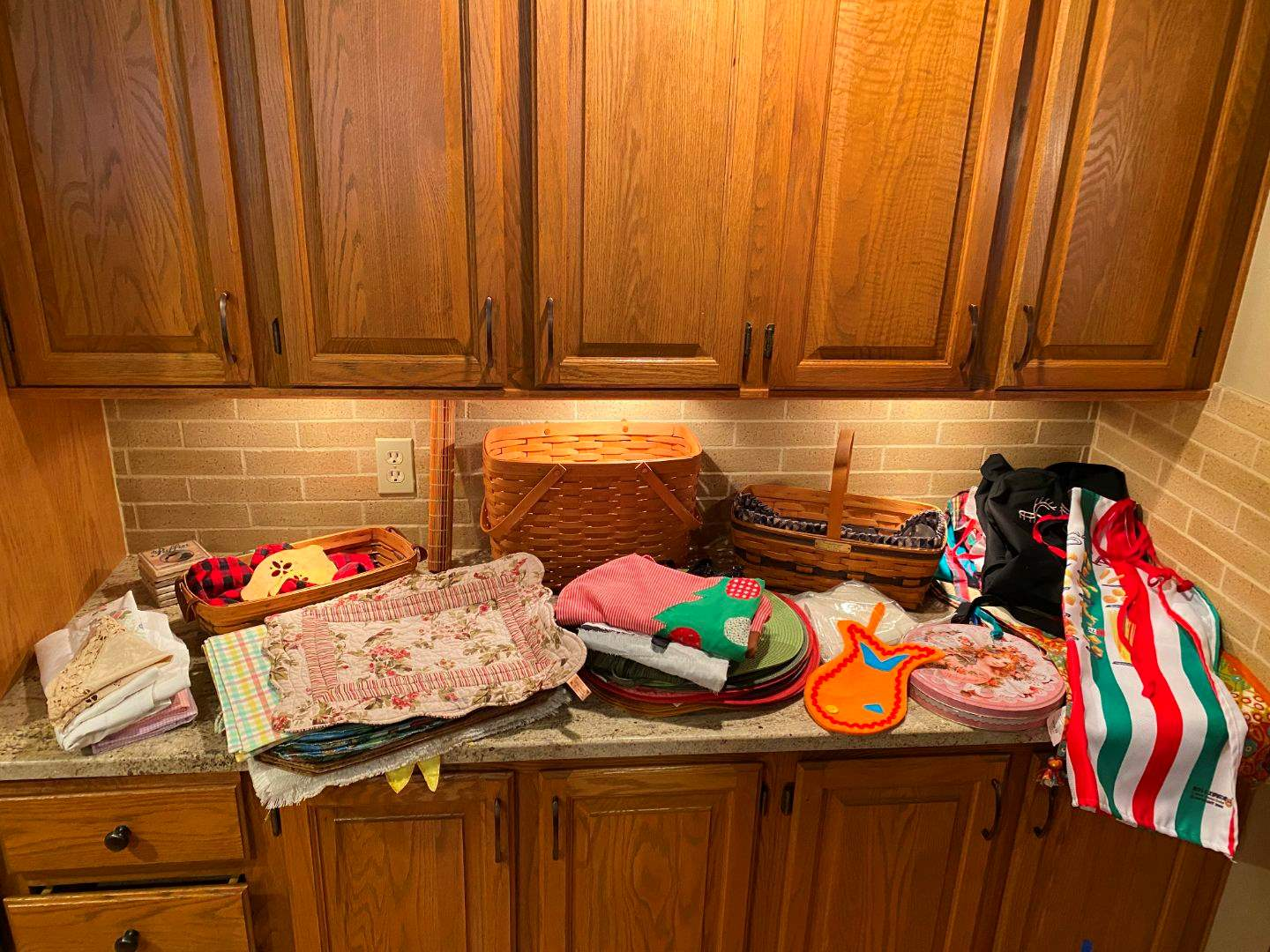 Lot # 77 - Selection of Placemats, Aprons, & Wood Baskets (main image)