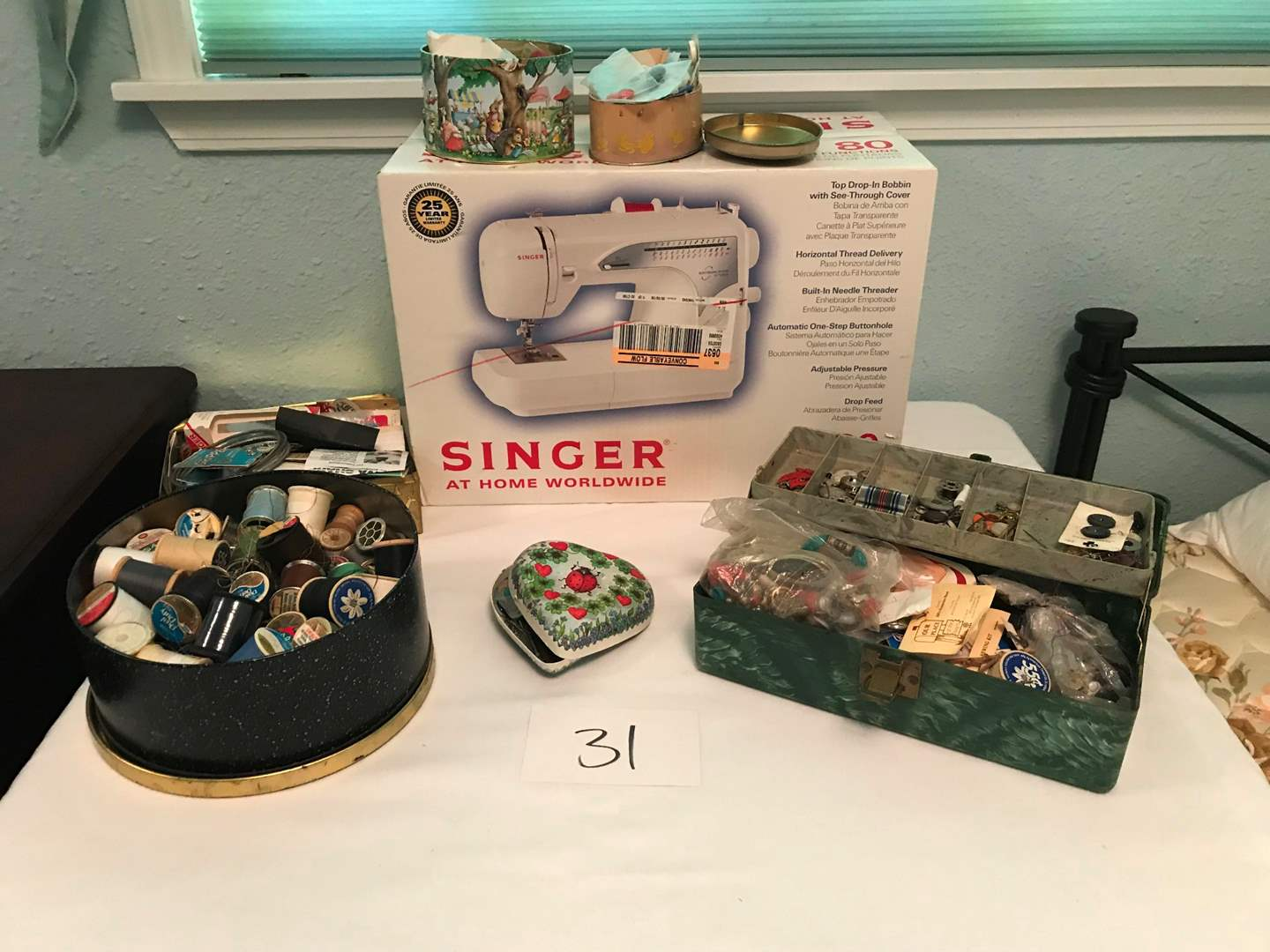 Lot # 31 - Brand new in box, Singer Sewing Machine Model #2662. Tins filled of sewing supplies/buttons (main image)