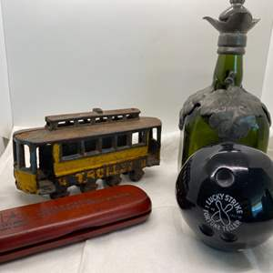 025 - Collectible Decor Items (Cast Iron Trolley, Glass & Pewter Decanter, Army Wood Pen and Pencil Set, Magic Bowling Bowl)