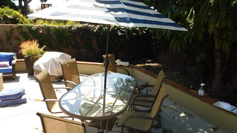 Lot # 369- Glass and metal patio table with 6 chairs, 1 ottoman and includes umbrella (main image)