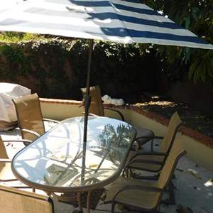 Lot # 369- Glass and metal patio table with 6 chairs, 1 ottoman and includes umbrella
