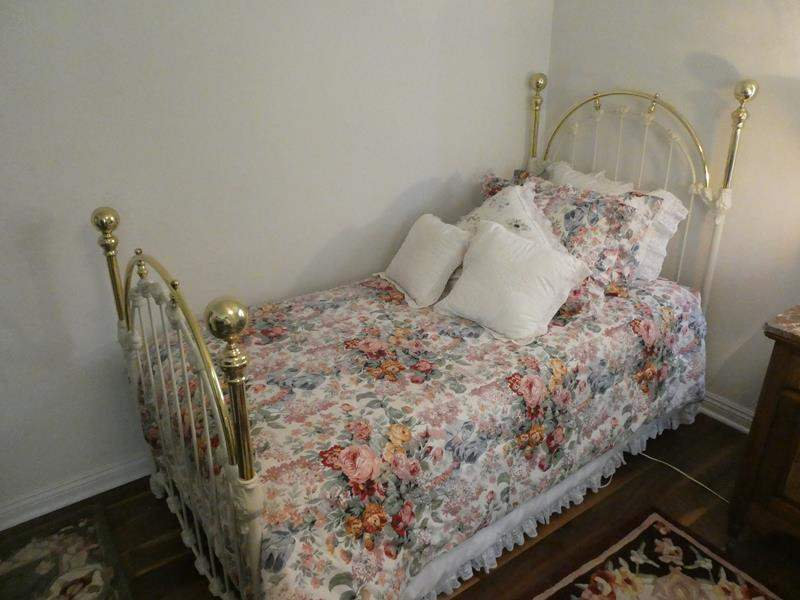 Lot # 119- Twin bed, brass and iron with mattress, comforter and pillow (main image)
