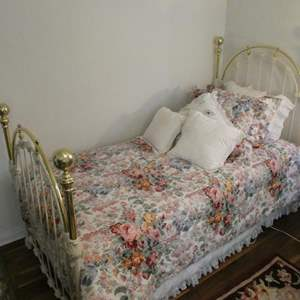 Lot # 119- Twin bed, brass and iron with mattress, comforter and pillow