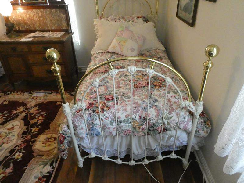 Lot # 120- Twin bed, brass and iron with bedding, mattress, and pillow (main image)