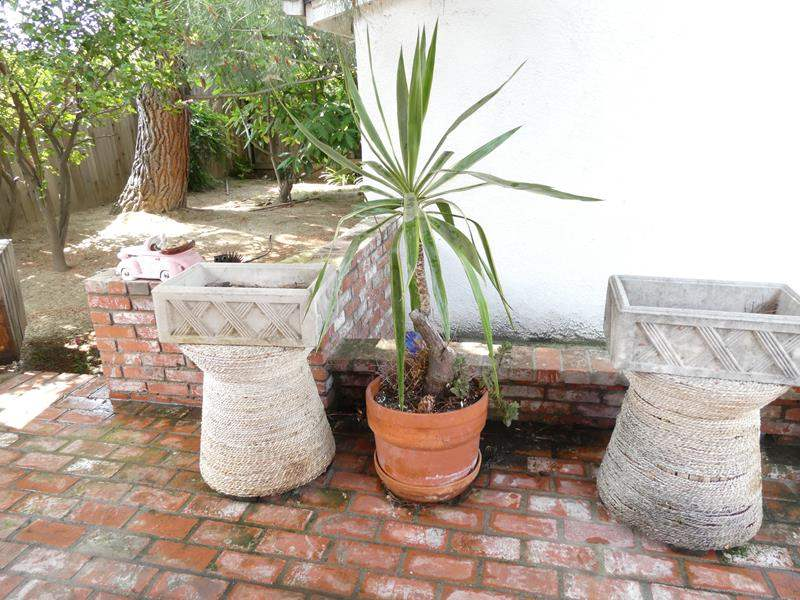 Lot # 317-Backyard decor, planters, wicker stands, cement planters (2) (main image)