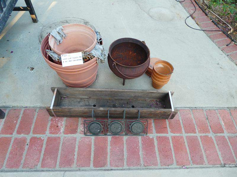 Lot # 457- Wood clay plastic pots and a large iron handled pot (main image)