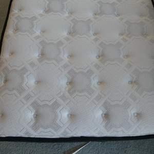 Lot # 36- Twin Costco mattress (new) & metal wheel bed frame