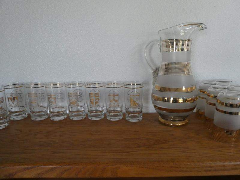 Lot # 52- Canada collector glasses (9) plus and pitcher gold trm and 6 matches glasses (main image)
