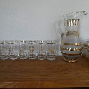 Lot # 52- Canada collector glasses (9) plus and pitcher gold trm and 6 matches glasses