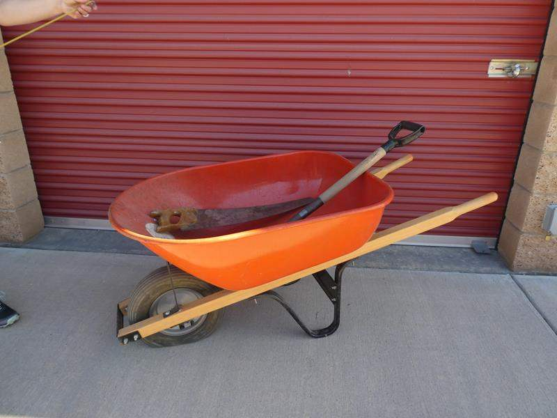 Lot # 35-Wheel barrel- great condition, just has flat tire, short flat nose shovel and saw (main image)