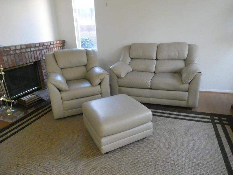 Lot # 105-Cream colored leather love seat, swivel chair and ottoman (main image)