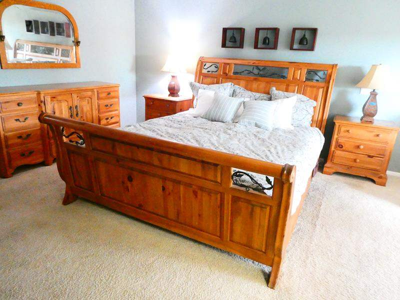 Lot # 36-  Cal King Size solid wood/wrought iron bed, Mattress and Bedding included (main image)