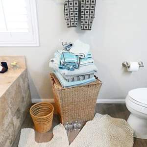 Lot # 43-Ocean Blue & Tan Bathroom Towels with basket, hamper, rugs  and candles