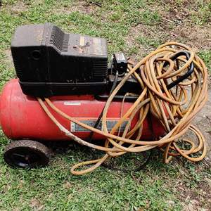 Lot # 216 4 horsepower 25 gallon Craftsman air compressor with a hundred foot hose works great