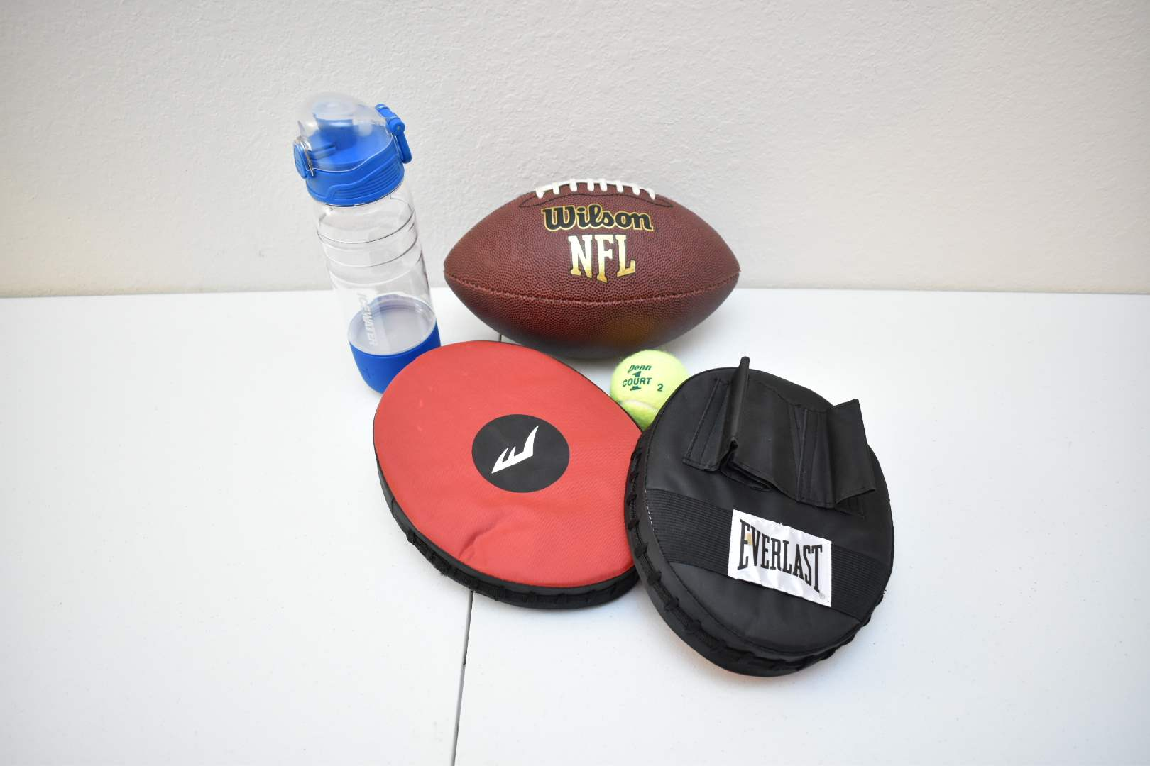 Sporting Items: Water bottle speaker, sparring mitts, football, tennis ball