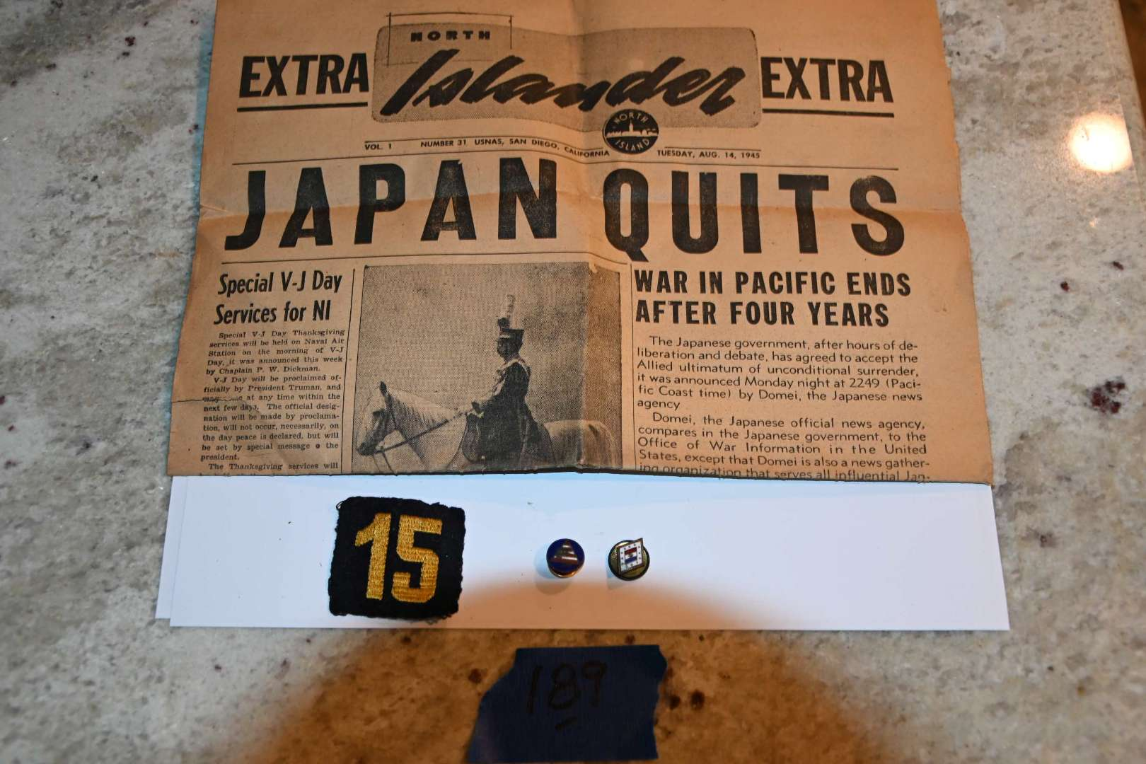 Lot # 189 WWII JAPAN SURRENDERS newspaper, military pins/patch