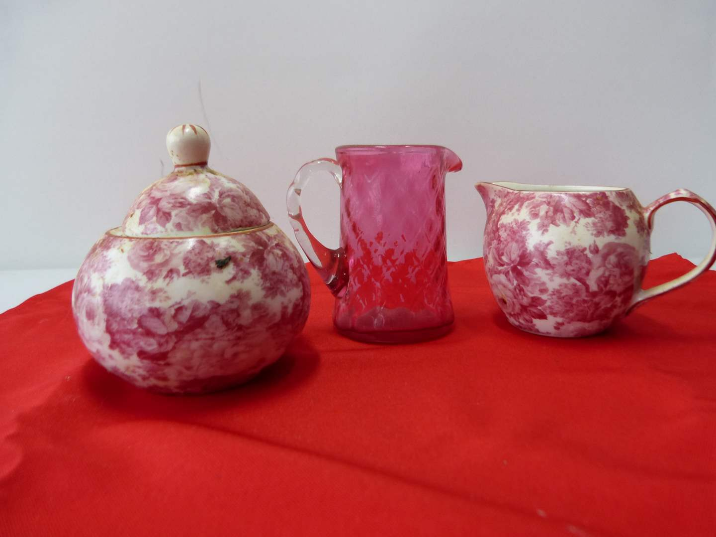 Lot # 56  Collection of pink/cranberry pcs to include creamer/sugar & hand blown cranberry miniature pitcher