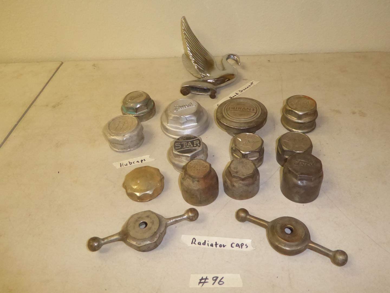 Lot # 96 - Vintage Radiator Caps, Hub Caps, Model A Gas Cap & Swan Hood Ornament (main image)
