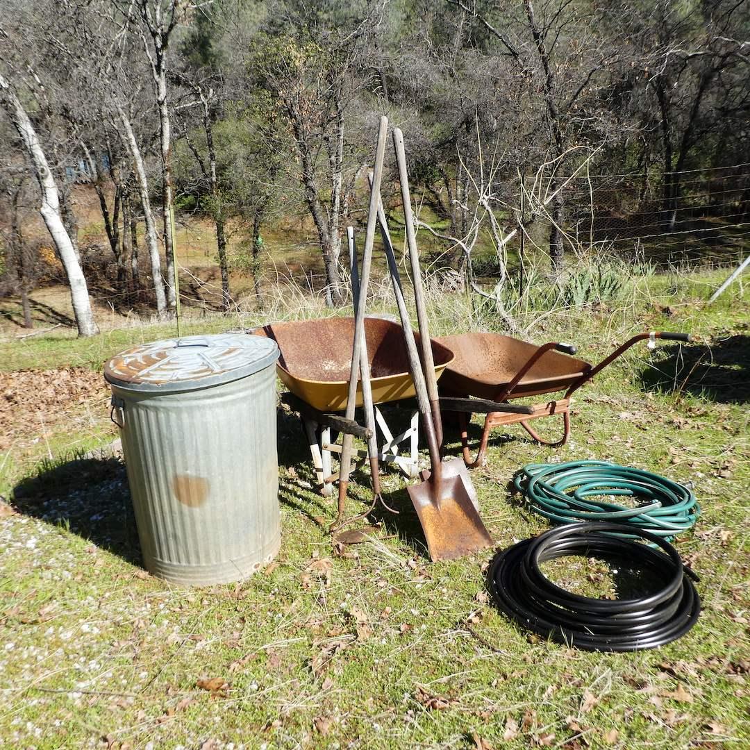 Lot # 242 - Two Wheelbarrows, Galvanized Trash Can, Hose and Yard Tools (Shovel, Hoe and Rake) (main image)