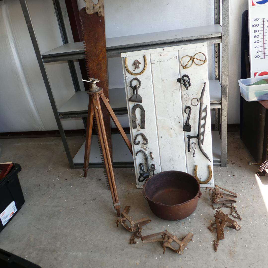 Lot # 141 - Old Transit Tripod, Vintage Lumber Hand Saw, 3 Legged Cast Iron Pot, Animal Traps & Western Horse Tack Display (main image)