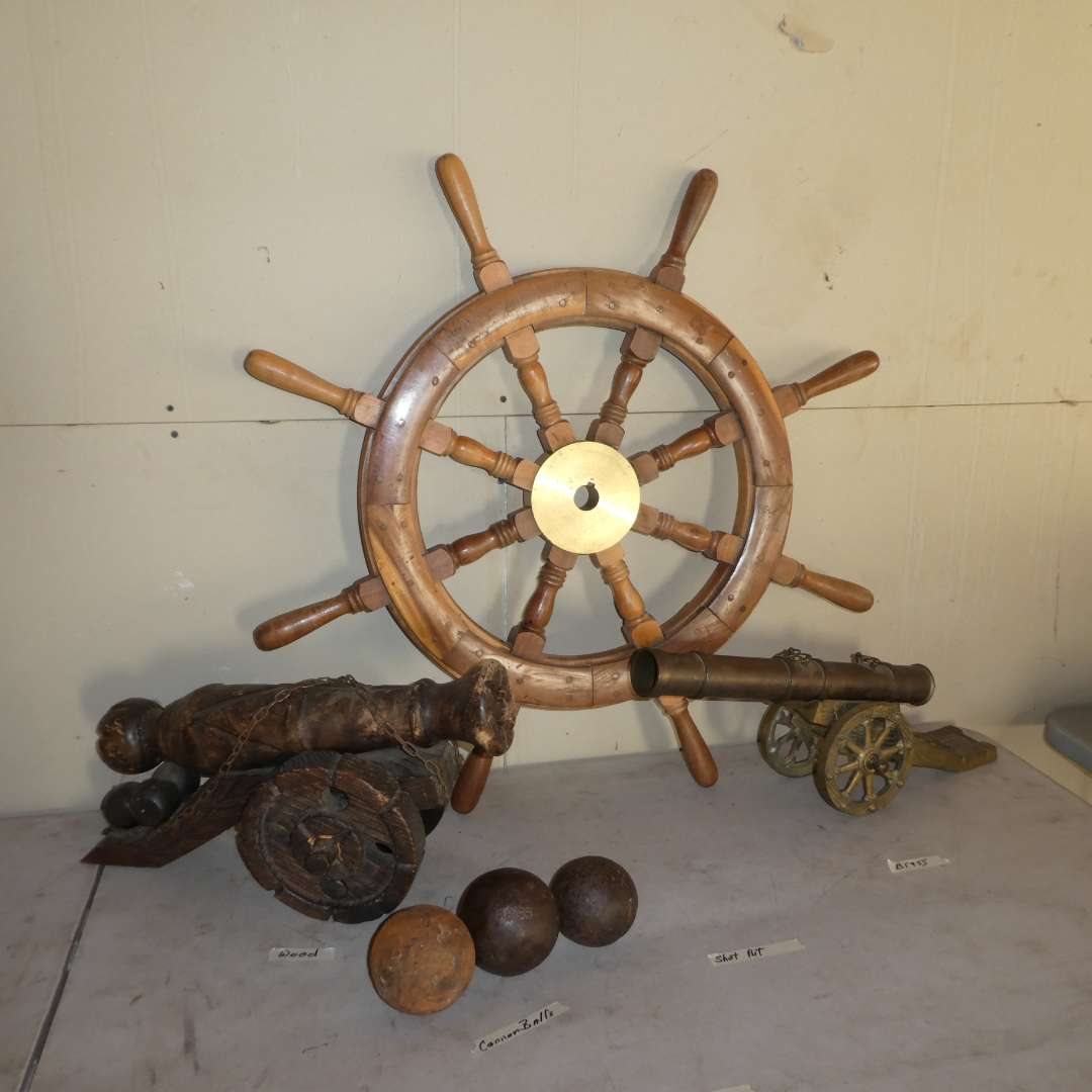 Lot # 11 - Wooden Ship Steering Wheel, Cannon Balls, Shot Put Ball, Brass and Wood Cannons (main image)