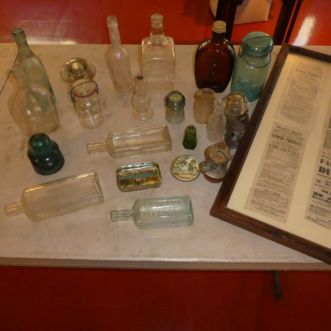 Lot # 72 - Vintage Embossed Glass Bottles, Framed Newspaper Cuttings, Early Miner Lamps, and Insulators  (main image)