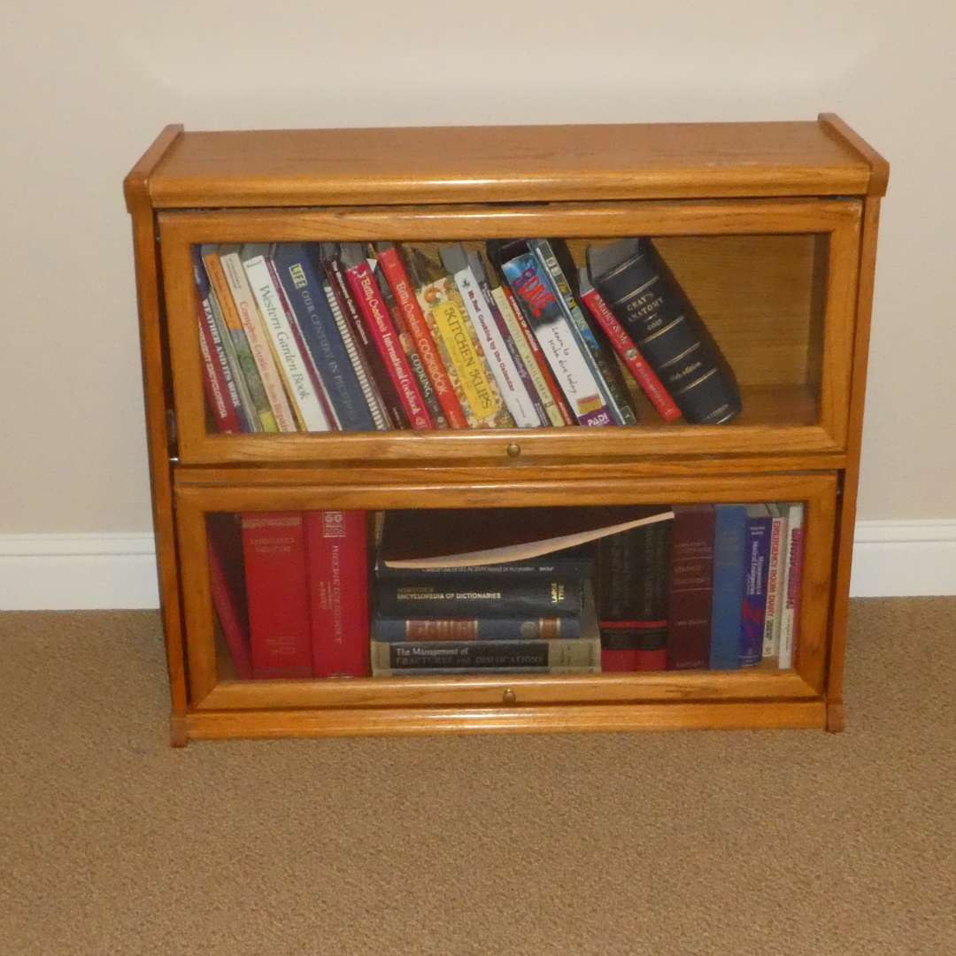 Lot # 37 - Small Solid Wood Bookcase w/ Sliding Glass Doors and a Variety of Books