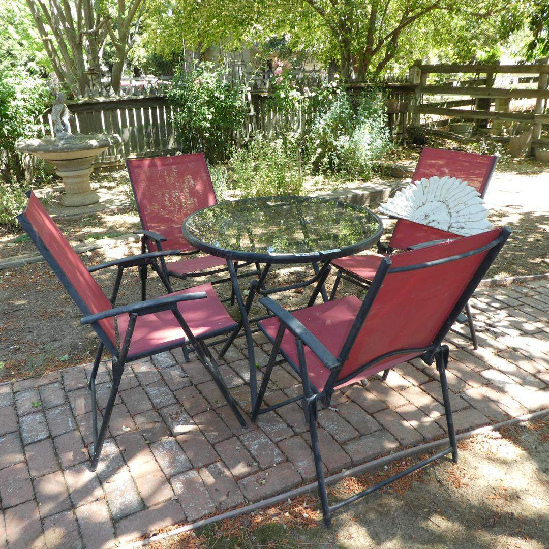 Lot # 110 - Glass Top Folding Patio Table & Four Folding Chairs (main image)