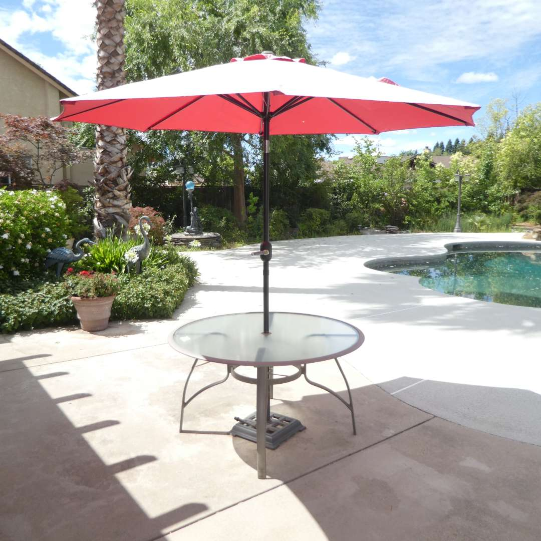 Lot # 410 - Round Metal and Glass Outdoor Table & Tilting Patio Umbrella w/ Wind Up Handle(Umbrella Is Sun Bleached on outside) (main image)