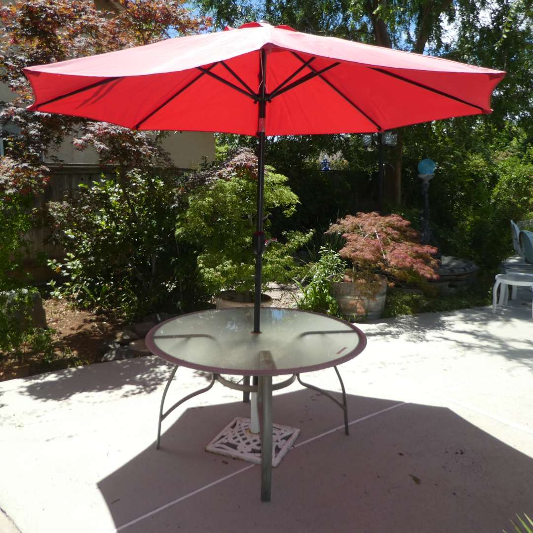Lot # 424 -  Round Metal and Glass Outdoor Table & Tilting Patio Umbrella w/ Wind Up Handle(Umbrella Is Sun Bleached on outside) (main image)
