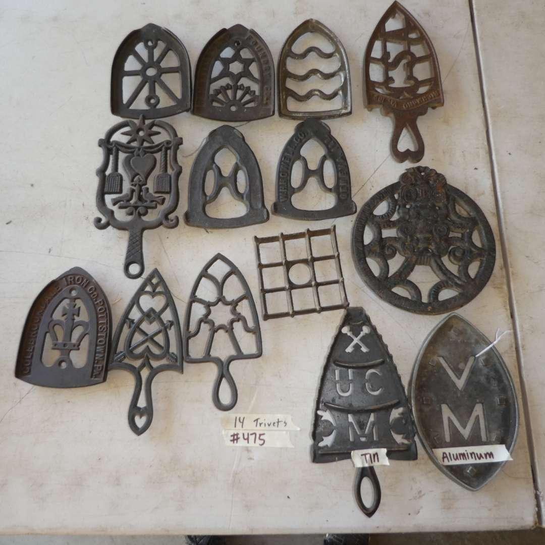 Lot # 475 - 12 Cast Iron Trivets, 1 Aluminum and 1 Tin (main image)