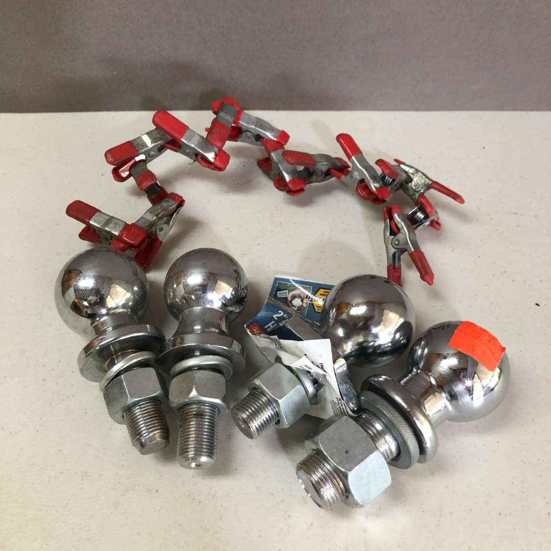 Lot # 180 - Four Trailer Hitch Balls and Spring Clamps (main image)