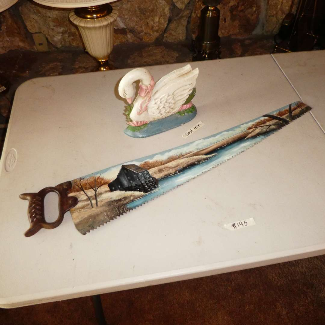 Lot # 195 - Cast Iron Swam Door Stopper/ Decor and & Decorative Hand Painted Saw w/ Cast Iron Handle  (main image)