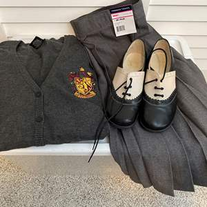"""Lot # 11- Hogwarts School Uniform: Harry Potter """"Gryffindor"""" Sweater, French Pleated Skirt (tag on), Shoes."""