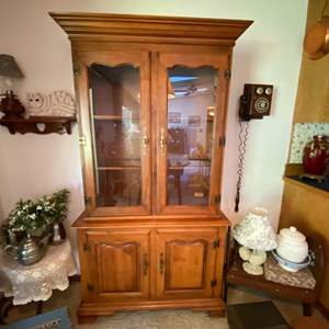 Lot # 107- Hard Rock Maple China Hutch with Glass Shelves and Light. Comes apart in Two Pieces. Nice Smaller Size. NOT Contents.
