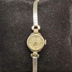 "Lot 93 - VINTAGE Ladies Mechanical Jeweled Watch ""Ofair Geneve 17 Rubis Antichoc Swiss"" on face, ""PLAQUEL 20 G K"" by stem."