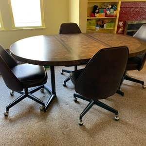 """Lot #100 - Retro 1970's Five Piece Dinette Set, Black Vinyl Swivel Chairs on Casters, Table Measures 63""""x 42"""" x 28""""h with Leaf"""