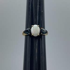 Lot # 66 - 10 karat gold ring with 1.5 carat opal and two .35 carat sapphires (2.1g total weight)