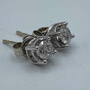 Lot # 2 - 1/4 carat diamond earring set in 14 karat gold surrounded by eight smaller diamonds