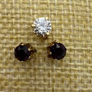 Lot # 17 - One .40C diamond earring and two 1/3 carat Garnet earrings