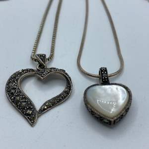 Lot #  17 - Two sterling necklaces and charms, marcasite heart and mother of pearl/black onyx heart (13.4g)