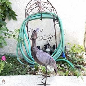 Lot # 106 - metal garden hose holder, hose and sculpture