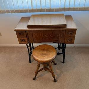 Lot # 250 - White treadle sewing machine and cabinet with adjustable clawfoot stool