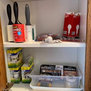 Lot # 267 - Laundry room cabinet: Batteries, lint rollers & light bulbs